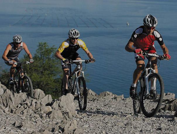 3 ragazzi in mountain bike in un percorso sul mare
