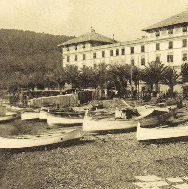 Historical photo of the beach with boats in front of the Hotel