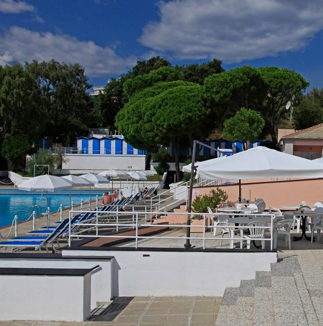 Зона со столиками и зонтиками с видом на панорамный бассейн отеля.
