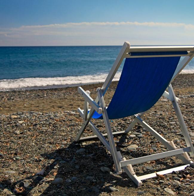 Фотография частного пляжа отеля с шезлонгом с видом на море.