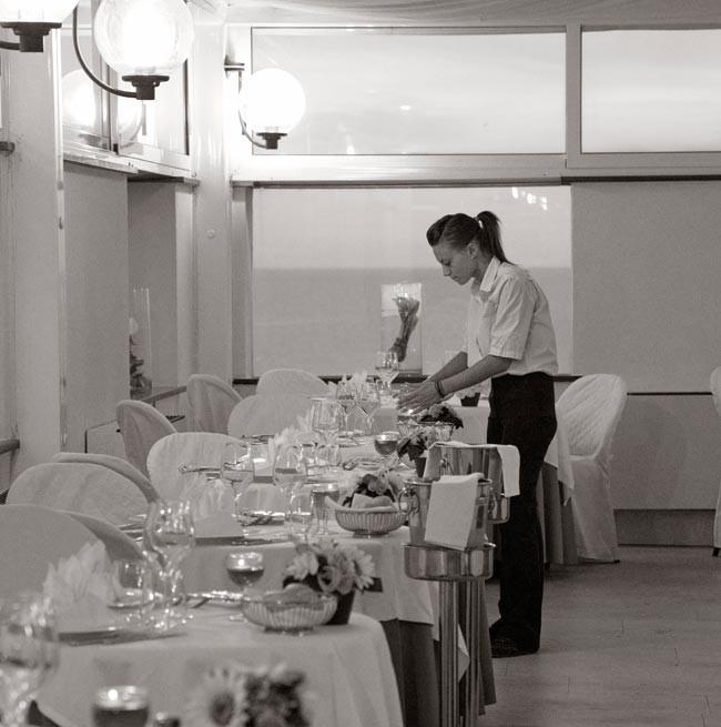Foto in bianco e nero di una cameriera che si occupa della mise en place dei tavoli del ristorante