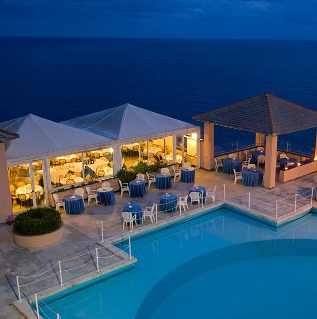 Foto notturna della piscina tonda vista mare dell'Hotel Punta San Martino