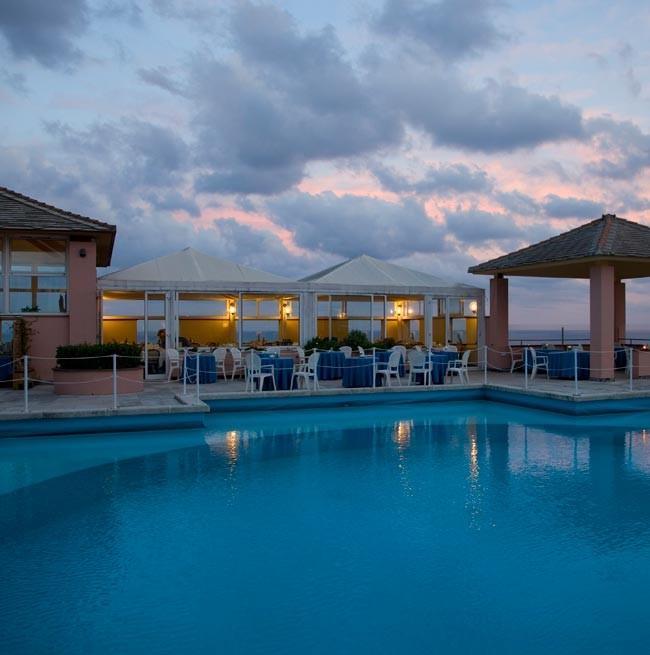 Foto al tramonto della piscina tonda con vista mare dell'Hotel