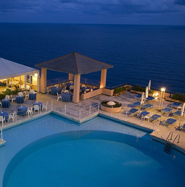 Evening photo of the round swimming pool overlooking the sea of the Hotel Punta San Martino